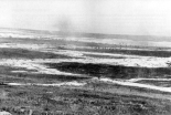 """1. Juli 1916, erster Tag der Schlacht an der Somme: Britische Truppen durchqueren das Niemandslands bei Mametz. Die weißen Flächen bestehen aus Kalk vom Ausheben der Schützengräben. Photo Q 87 des """"Imperial War Museum"""", Public Domain (nach: Wikimedia Commons)."""